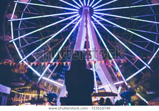 girl-staying-near-ferris-wheel-600w-723518749.jpg